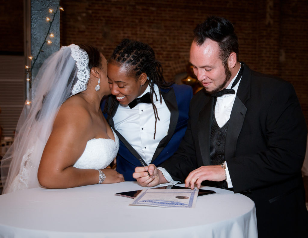 The brides signing the marriage license -same sex weddings